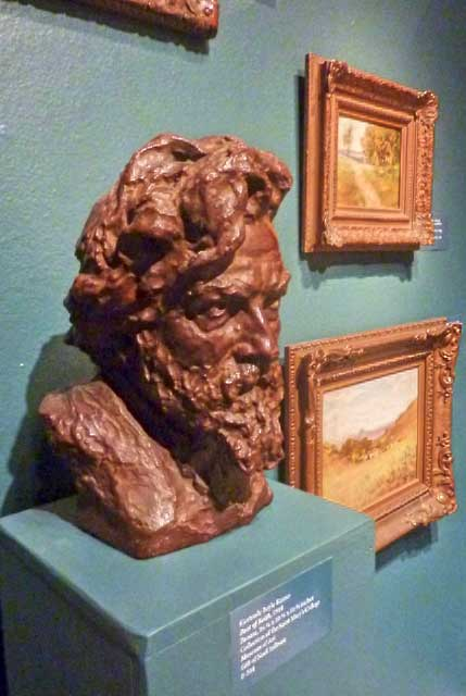 A bust of William Keith is grouped with several of his smaller, gold framed, paintings, in the exhibit.