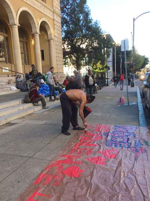 Homeless evictees rest briefly on the Post Office steps before postal police evict them again.