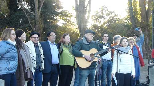 "Hundreds gathered at Martin Luther King, Jr. Civic Center Park at 7:00 AM today, November 18,  to greet the dawn and show Berkeley solidarity after the national election results by forming a giant peace symbol.  Mayor elect Jesse Arreguin and Councilmember Linda Maio and incoming Councilmember Sophie Hahn spoke, and joined with other elected officials in a line behind noted Berkeley folk singer Gary Lapow who sang his own version of ""Hallejah"" for and with the crowd."