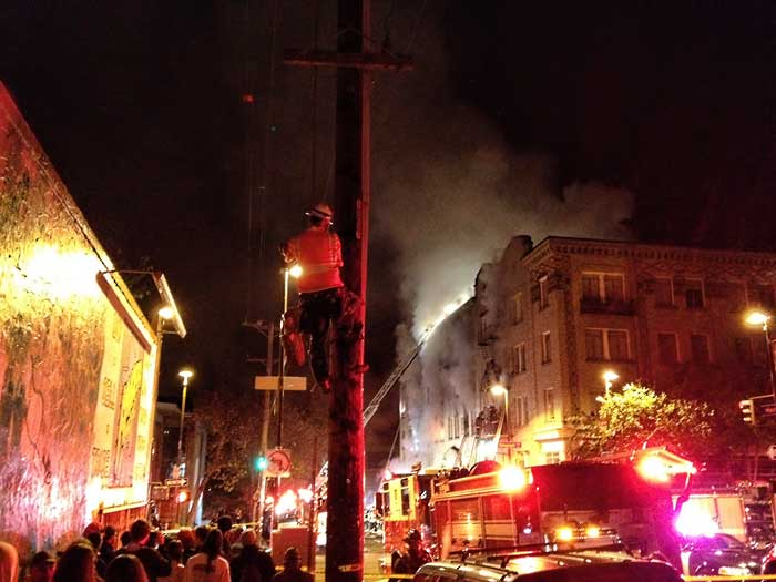 A lineman works above the heads of the crowd which has gathered on Haste Street.