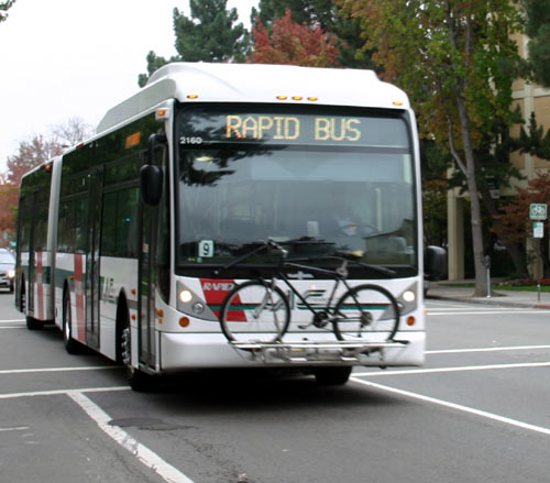 A Van Hool bus runs down Telegraph Avenue where a rapid transit system is proposed.