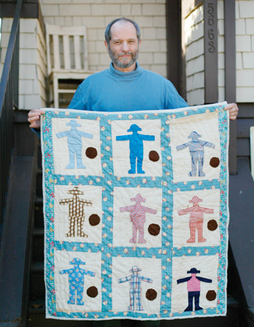 Jakob Schiller: Eli Leon holds one of his favorite quilts from his collection. Each square, using different fabric from the 1930s, pictures a boy bouncing a ball..