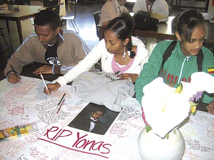 Berkeley High students Abdul Shemse, Selamawit Mersha and Gesha Melkamu write condolence messages on Yonas Mehari's memorial on Wednesday. The students, who are members of the Ethiopian Eritrean Students Union, are gathering funds for Yonas's family. Photograph by Riya Bhattacharjee.