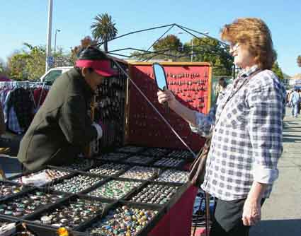 Sher Hickerson tries on Tibetan jewelry at vendor Tseten Khangsar's booth.