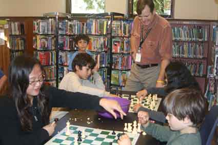 Librarian Will Marston looks on as members of the teen chess club battle over the boards at the north branch of the Berkeley Public Library.