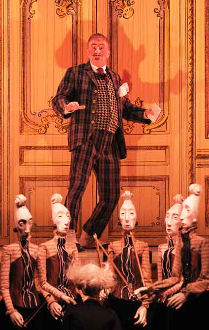 Geoff Hoyle in an orchestra of marionettes