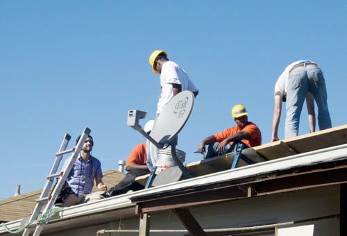 Young RichmondBUILDs solar installation trainees take a breather as they install panels on the roof of a Richmond home.