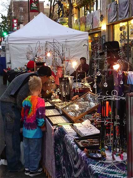 Telegraph Avenue Holiday Street Fair shoppers examine the crafts on display in front of Rasputin's.