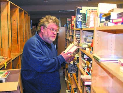 Black Oak Books owner Gary Cornell stocks shelves in time for the store's Thursday re-opening.