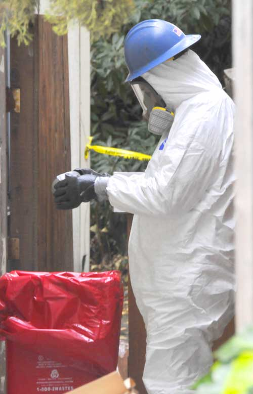 A crime scene cleanup technician finishes donning his protective gear as he prepares to work on the Ashby Avenue room where police found a body buried behind a wall.